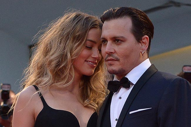 "US actor Johnny Depp and his wife US actress Amber Heard arrive for screening of the movie ""Black Mass"" presented out of competition at the 72nd Venice International Film Festival on September 4, 2015 at Venice Lido. AFP PHOTO / TIZIANA FABI (Photo credit should read TIZIANA FABI/AFP/Getty Images)"